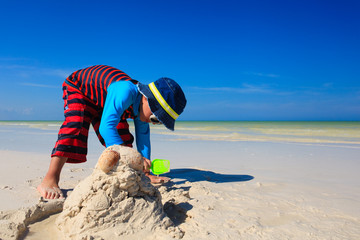 little boy digging sand on tropical beach