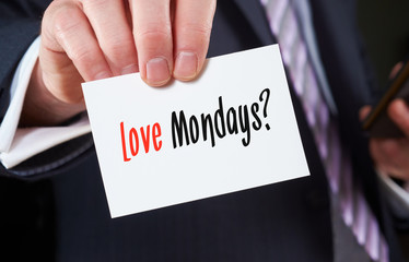 A businessman holding a business card with the words,  Love Mon