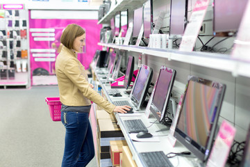 woman buying desktop in store
