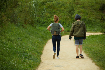 Young couple of hikers walking on a mountain trail together