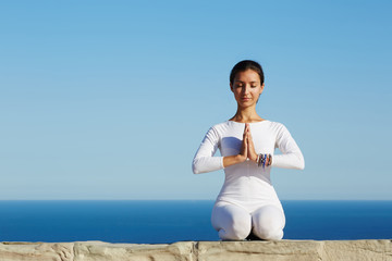 Gorgeous smiling woman practicing  yoga meditation outdoors