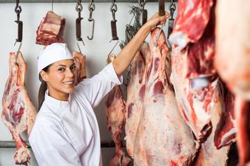 Female Butcher Hanging Meat In Butchery