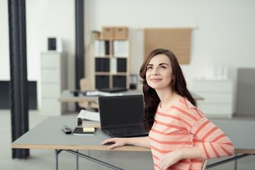junge frau arbeitet am schreibtisch mit laptop