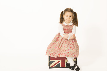 Lovely happy little girl sitting on a old suitcase waiting