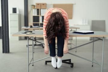 frau im büro sitzt auf dem tisch und lässt den kopf nach hängen