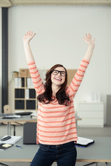 lachende frau im büro streckt die arme nach oben