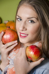 loseup of pretty girl holding two pomegranates next to her face