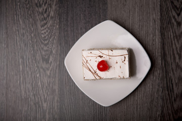 Creamy cake with cherry, top view