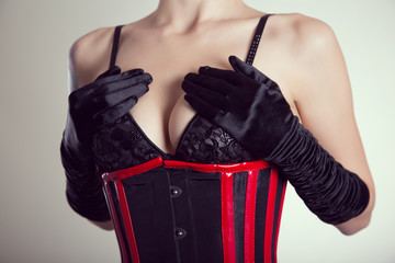 Close-up shot of busty fetish woman in black bra and corset