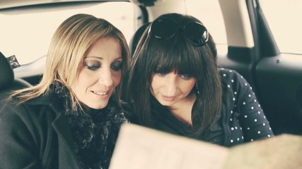 Two Women Reading Map in the car