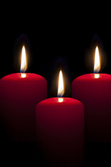 red candles lighting in the darkness