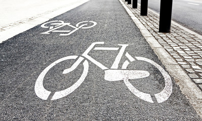 White painted bike path signs on asphalt.