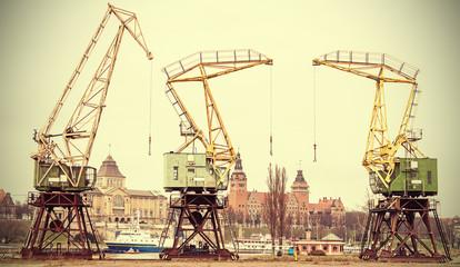 Retro stylized picture of cranes in Szczecin City, Poland.