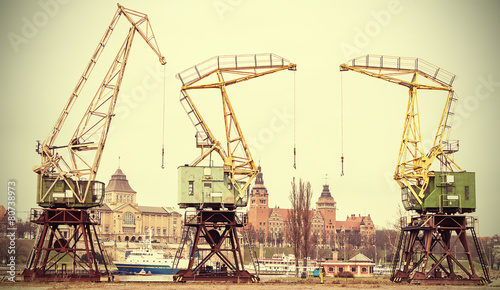Retro stylized picture of cranes in Szczecin City, Poland. - 80738973