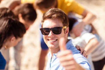 happy young man in sunglasses showing thumbs up