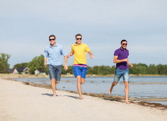 smiling friends in sunglasses running along beach