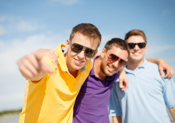 smiling friends in sunglasses pointing at you