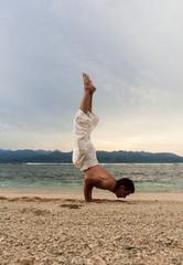 man doing yoga on the sand beach with sunset
