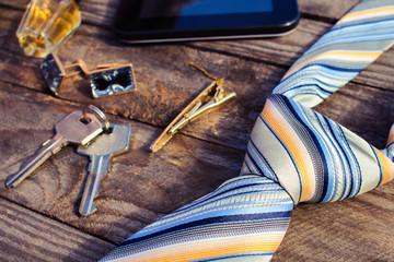 Men accessories: tie, cufflinks, tablet, perfume and keys