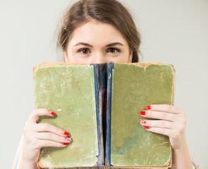 teen girl behind open vintage book