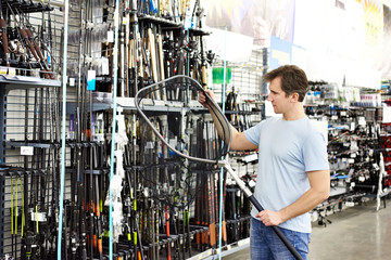 Man chooses landing net for fishing in sports shop