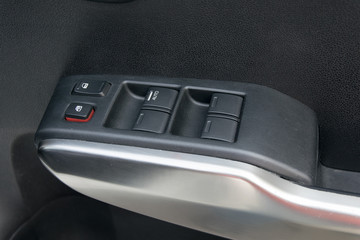 car interior details of door handle with windows controls and ad