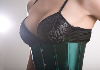Close-up shot of sexy young woman in black bra and green corset