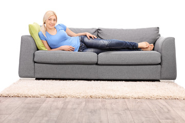 Beautiful blond woman lying on a modern gray sofa