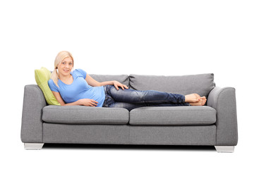 Pretty woman lying on a modern gray sofa