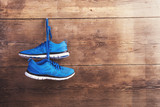 Fototapety Pair of sneakers hang on a nail on a wooden fence background