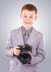kid holding a dslr camera on a blue background
