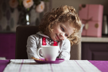 Little curly girl with cup sitting at the table