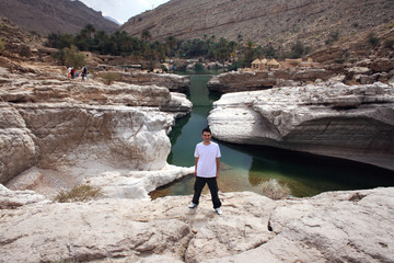 Man standing at a rock pool in Wadi Bani Khalid