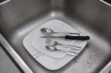 Kitchen sink with used eating utensils