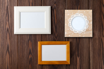 Photo frames on wooden wall