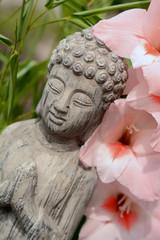 Grey buddha statue in flower garden with bamboo