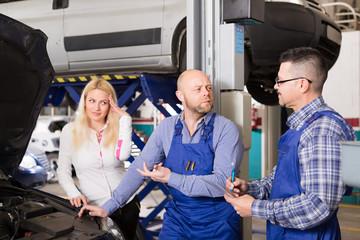 Woman and two auto mechanics