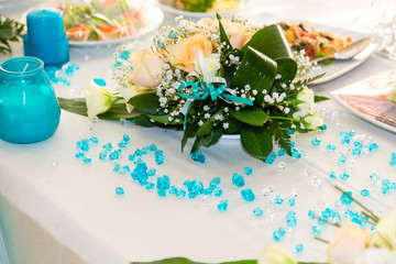 Bouquet of roses and turquoise decoration on the wedding table