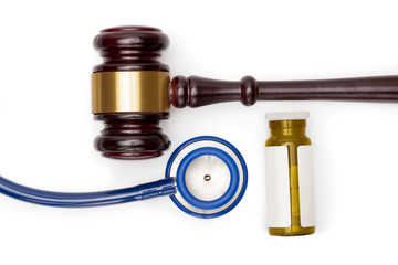 Judge gavel, pills bottle and stethoscope on white backround