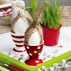 Easter eggs with sackcloth rabbit ears in the red egg cups