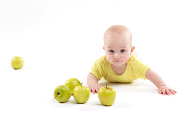 smiling baby lying on the background to include apples