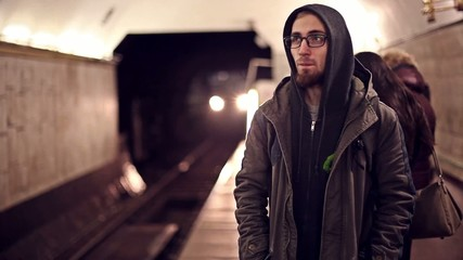 the guy is waiting for a train at a subway station