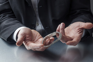 male appraiser's hands with diamond bracelet