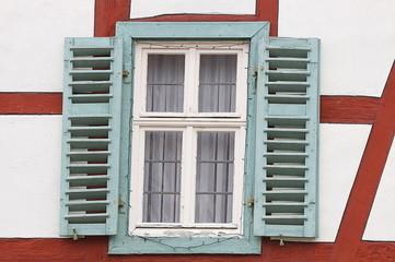 Altes Haus mit rotem Fachwek und grünem Fenster