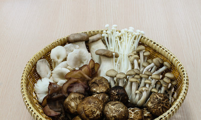 Oriental mixed mushroom in the basket on wood background