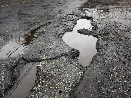 Big pothole caused by freezing and thawing - 80750547