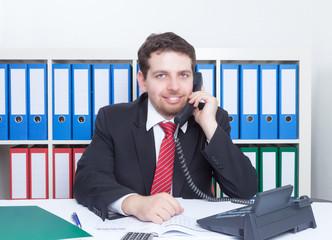 Mann im Büro am Telefon schaut zu Kamera