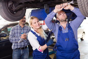 mechanic and assistant working at auto repair shop