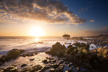 Old shipwreck long exposure on the rocks sunse