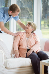 Male nurse assisting retired woman